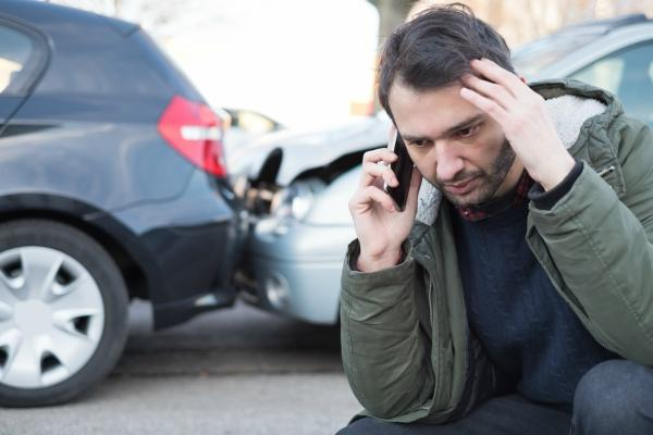 Man in front of a car wreck